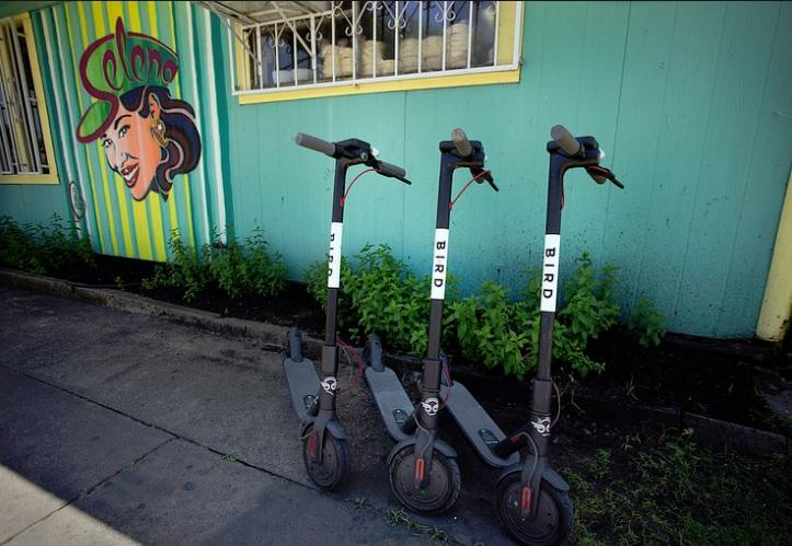 Three electric scooters owned by rental company Bird ready for riders in Austin.