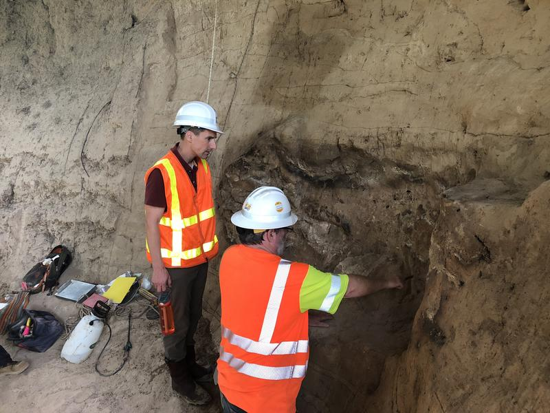 Scott Pletka, left, and Jim Abbott of TxDOT's archaeological team examined ancient remains found in an earthen wall during a bridge inspection in July.