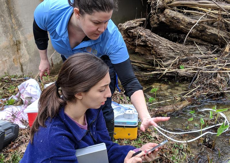 Jessica Quintanilla works with SwRI's Rebecca Nunu to take readings from the water sensor via bluetooth connection.