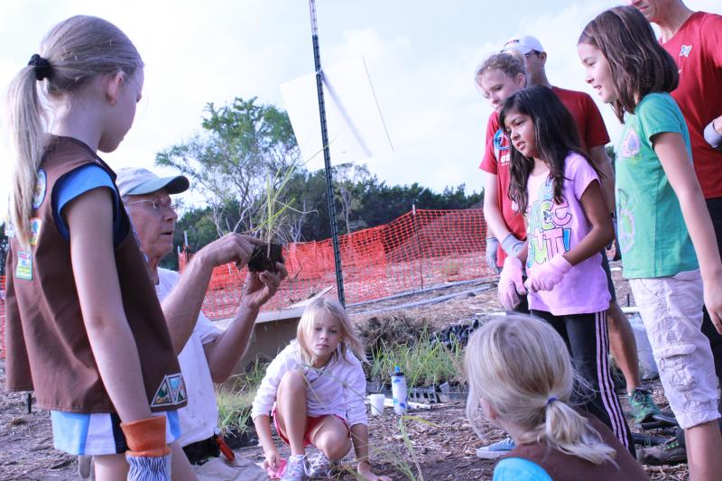 A Brownie troop gathers around to learn about planting grass plugs at Hardberger Park for National Public Lands Day on October 6.