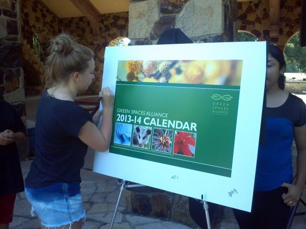 Lauren Szymanski, one of more than 20 contributing youth photographers, signs a calendar poster at Brackendridge Park's Joske Pavilion, where the Picture Your World Calendar was unveiled Monday, July 30, 2013