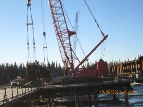 A big crane prepares to hoist a couple of 165-foot, 72-ton girders onto piers near the west bank of the Tanana River late last month. The trucks to the left are parked on a smaller, temporary bridge built last year to enable workers and equipment to get across the river and to work on the main structure.