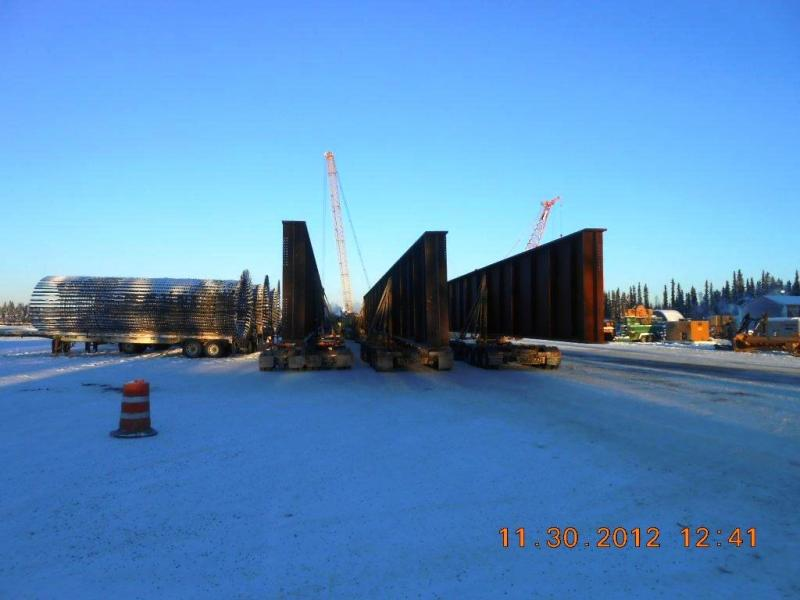 After navigating the road leading to the construction site, the three-truck convoy hauling massive bridge girders assemble and await their turn pulling up alongside a crane, which will unload the girders.