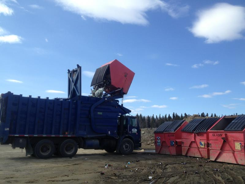 A dump truck empties dumpsters filled with glass.
