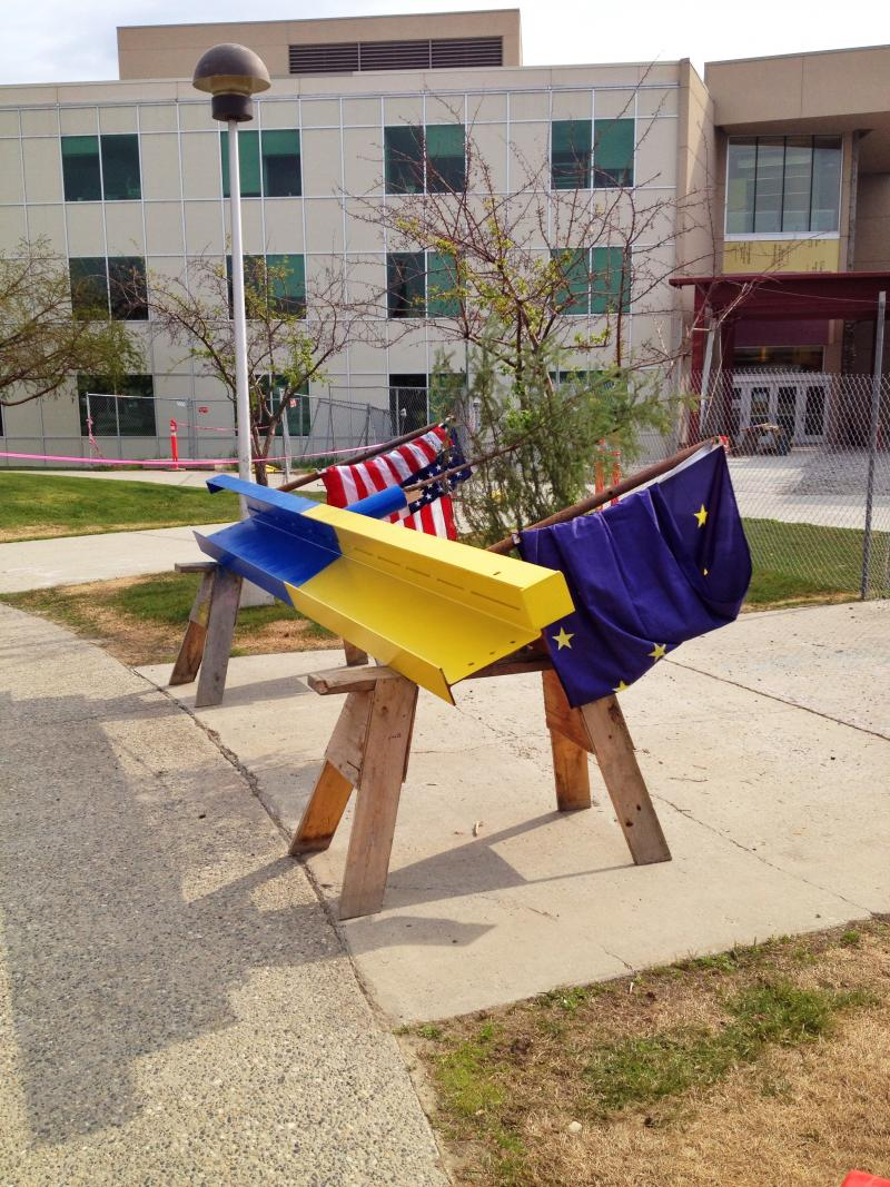 The last piece of steel, outfitted with an Alaskan flag, a US flag and a tree.