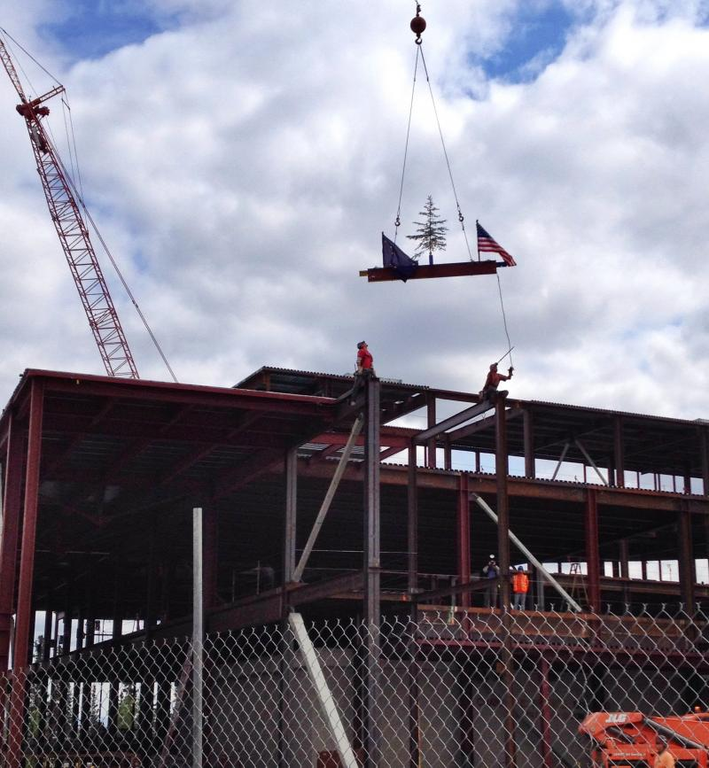 The last piece of steel is lowered toward the building.