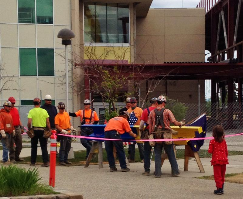 Iron workers sign the piece of steel.