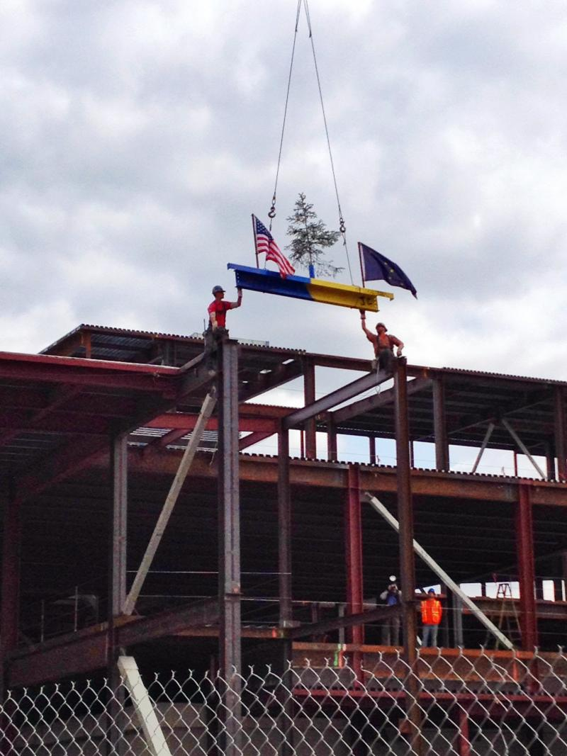 Workers pull the last piece of steel into place.