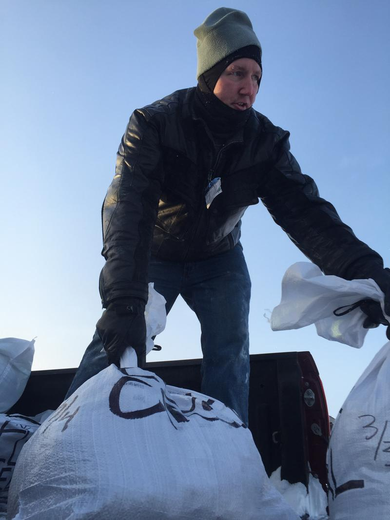 A volunteer helps unload drop bags from the back of a musher's pickup truck