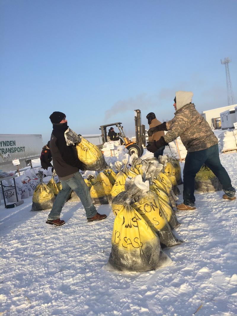 Volunteers organize drop bags after they are collected from mushers