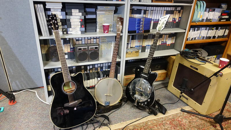 Bow's collection: acoustic guitar, claw hammer banjo with an extra string added, a Bow Thayer electric original Bojotar