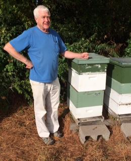 University of Arkansas Entomologist Dr. Donald Steinkraus stands next to several research honeybee hives on the UA campus.