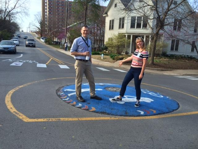 City of Fayetteville Parks & Recreation forester, Lee Porter, right, poses with Dane Eifling, Sustainability & Resilience division's bicycles and pedestrians coordinator, on a hand-painted mini-roundabout.
