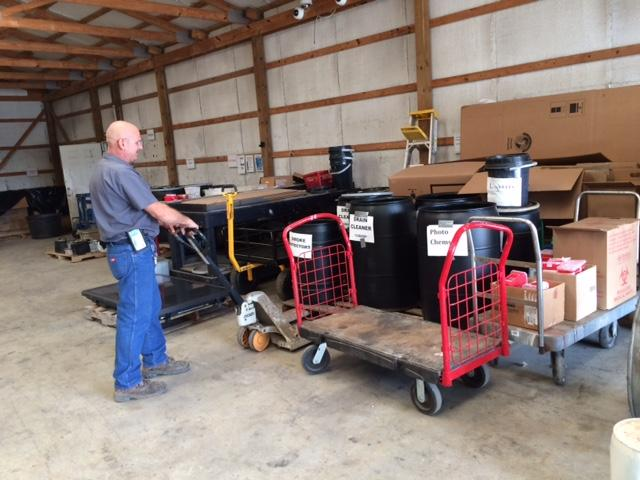 Washington County Household Hazardous Waste Collection Center operator Pete Trollinger moves a cart inside the facility.