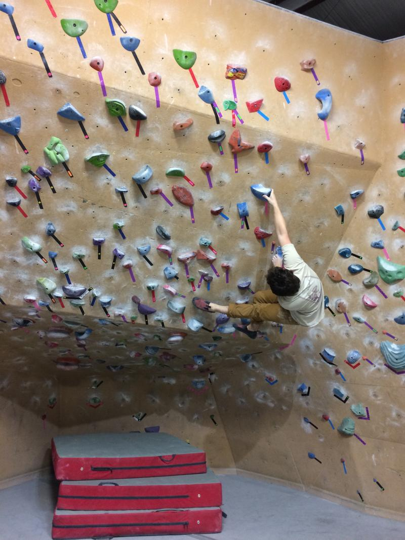 Jason Groves executes a compliated bouldering maneuver inside his business, Ozark Climbing Gym in Springdale.