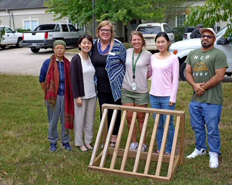 Patty Sullivan, third from the left, stands with Kelsey Miller, city of Fayetteville bicycle department staff, and four Ozark Literacy Council student cyclists, by their newly donated used bike rack.