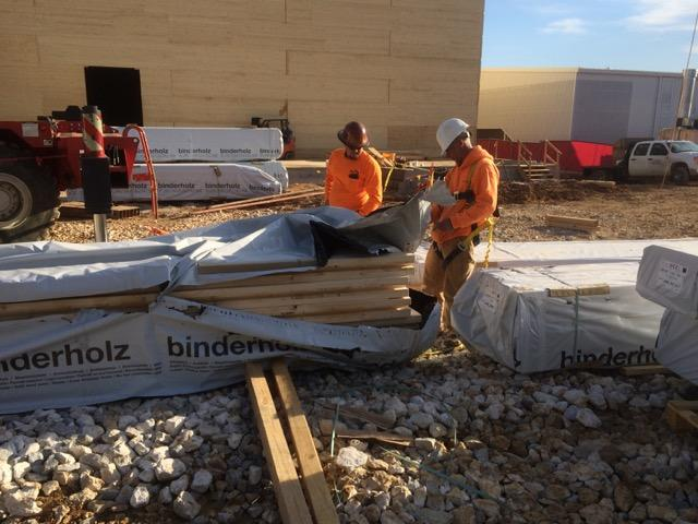 Workers unwrap prefabricated cross-laminated timber panels.