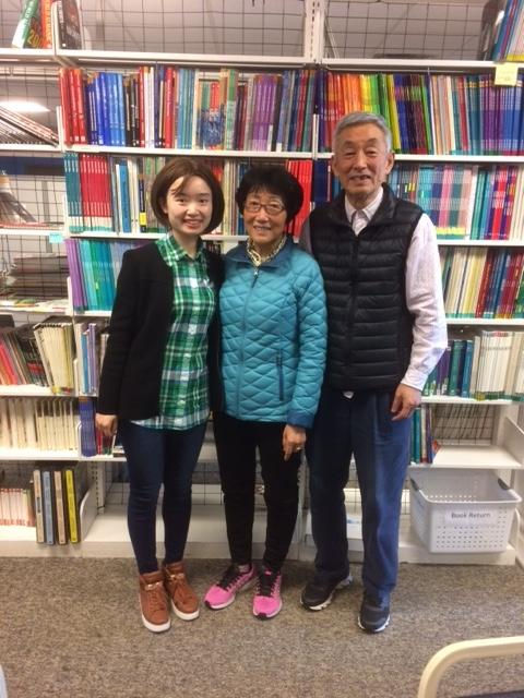 Chinese Translator Bing Bing Yang stands with Dr. Limin Zhang and Dr. Fuquan Ding in the library at Ozark Literacy Council.
