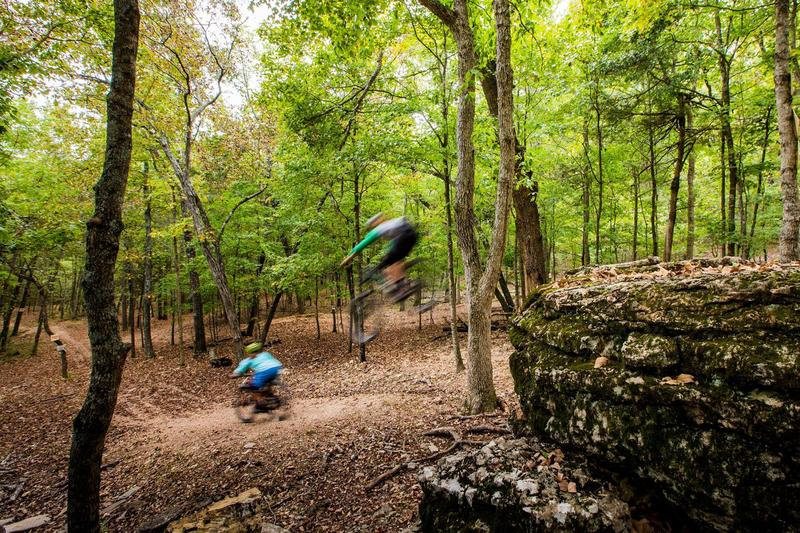 Rider take the jump line on the original downhill trail at Lake Leatherwood. Current construction will add six more downhill trails in the area.