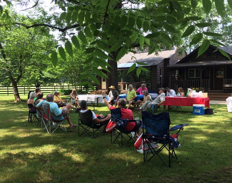 Members of the Mulberry River Society gather for an outdoor picnic business meeting.