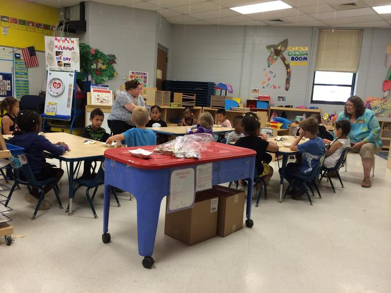 Asbell Elementary School pre-K children enjoy an afternoon snack with teacher Amber King and paraprofessional Sheila Wright.