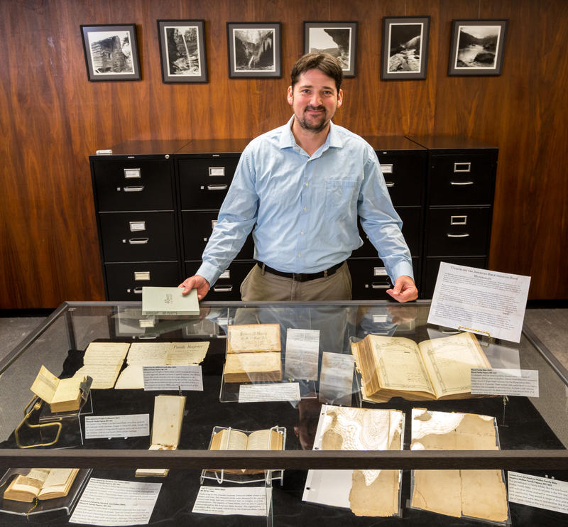 Joshua Youngblood with a collection of rare books at Mullins Library Special Collections.
