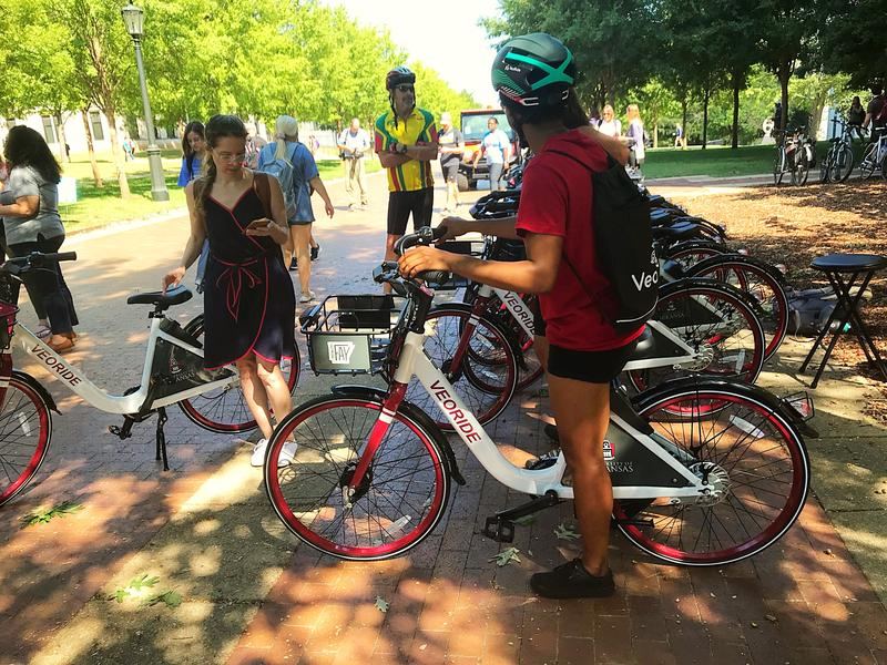 Bike share launch attendees figure out how to unlock and use the system's bicycles.