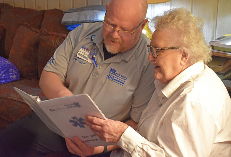 Jason Moshier sits with Julie Younes, an 87-year old Community Paramedic program patient.