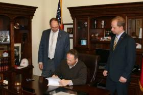 Lt. Gov. Mark Darr signing the bill that makes the concealed carry list private, surrounded by Sen. Bruce Holland (left) and Rep. Andy Davis (right).