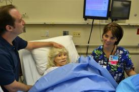 Peter Leake (left), playing the role of husband to the expectant simulated patient named Noel, and Julie Warner, R.N., wait for the delivery to begin.