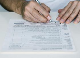 person filling out tax form