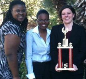 From left: Marla Cole, Angela Johnson and Dr. Allison Merrick hold a trophy after competing at the Texas Regional Ethics Bowl in San Antonio, Texas.