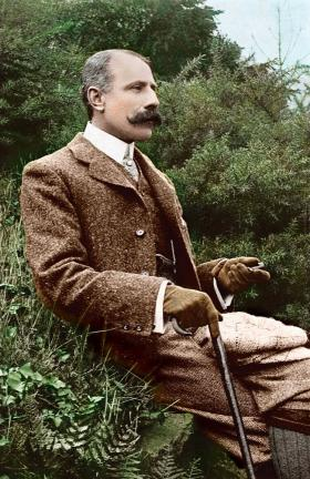 Edward Elgar is surrounded in this colorized photo by lush greenery.