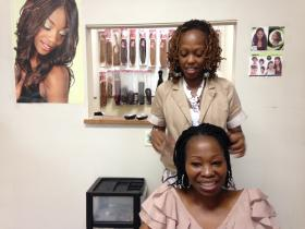 Shop owners Nivea Earl and Christine McLean, the two Arkansas plaintiffs in the lawsuit, give a hair braiding demonstration.