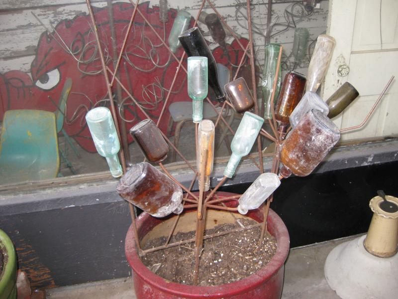 "A rustic ""bottle bush"" adorns the outside of a retail shop."
