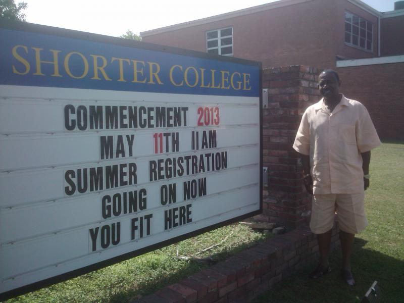 Cedric Hawkins, Shorter College's graduate for 2013 stands near marquee.