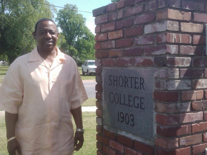 Cedric Hawkins, Shorter College's graduate for 2013 stands near a cornerstone from 1903