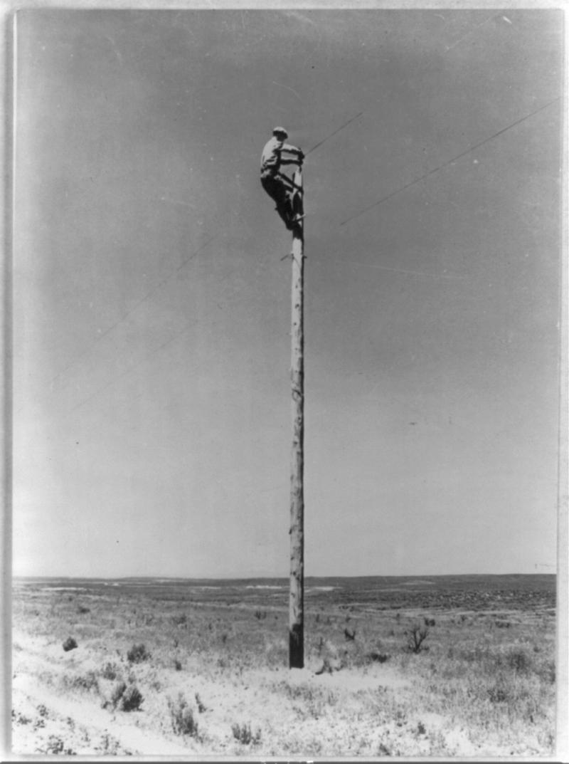 A lineman from the Rural Electrification Administration hangs a power line.