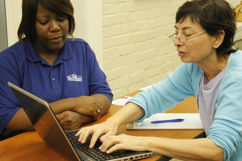 A guide works with a woman signing up for coverage Tuesday at the Clinton School of Public Service.