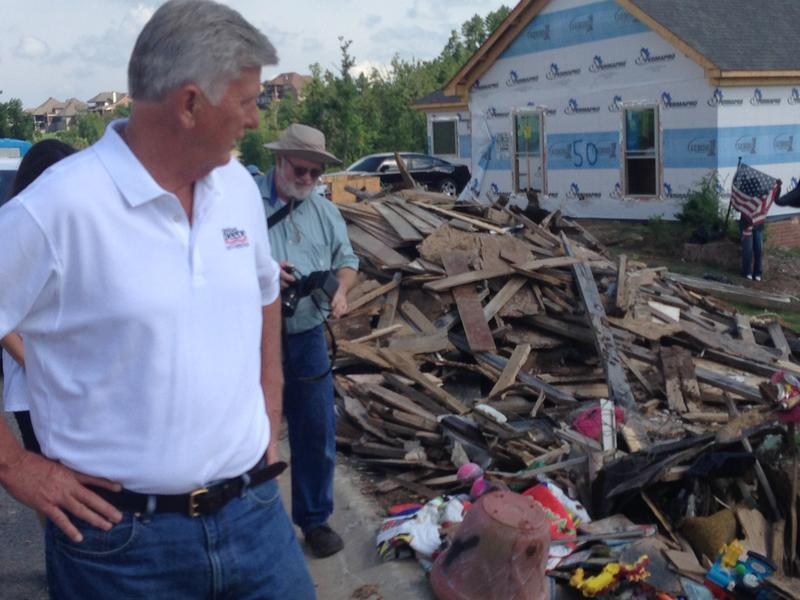 Governor Mike Beebe Looks At Debris With Construction In Background