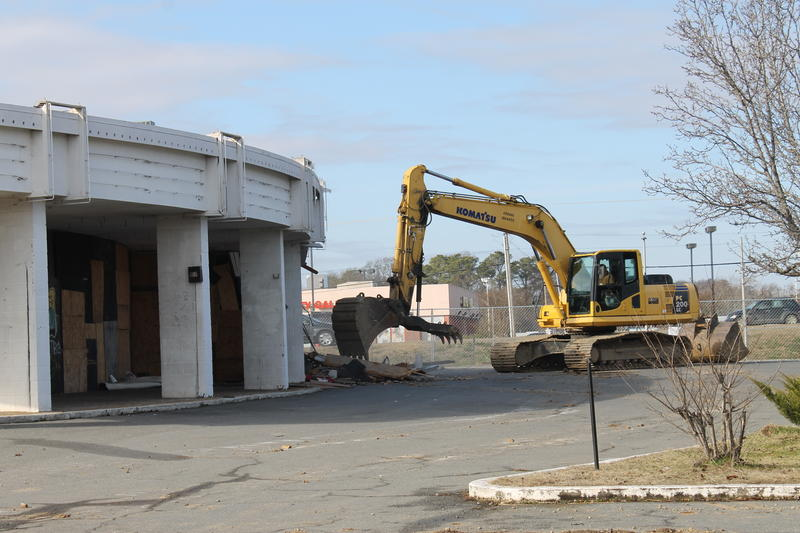 A second excavator begins working on the other side to tear down the theater.