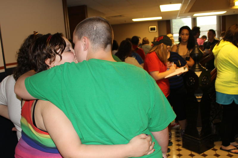 A couple kisses while waiting in line at the Pulaski County Circuit Clerk's office to apply for a marriage license.