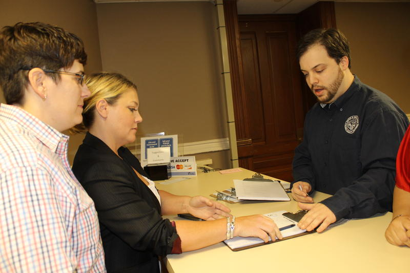 An employee in the Pulaski County Circuit Clerk's office gives a same-sex couple the form to apply for a marriage license.