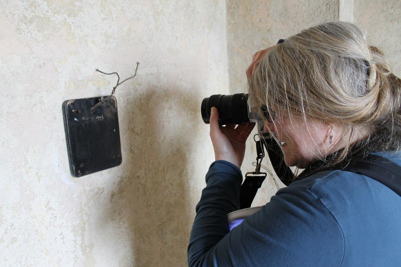 Rita Henry photographs an item on the wall that includes the date Nov. 8, 1913, around the time the hotel opened.