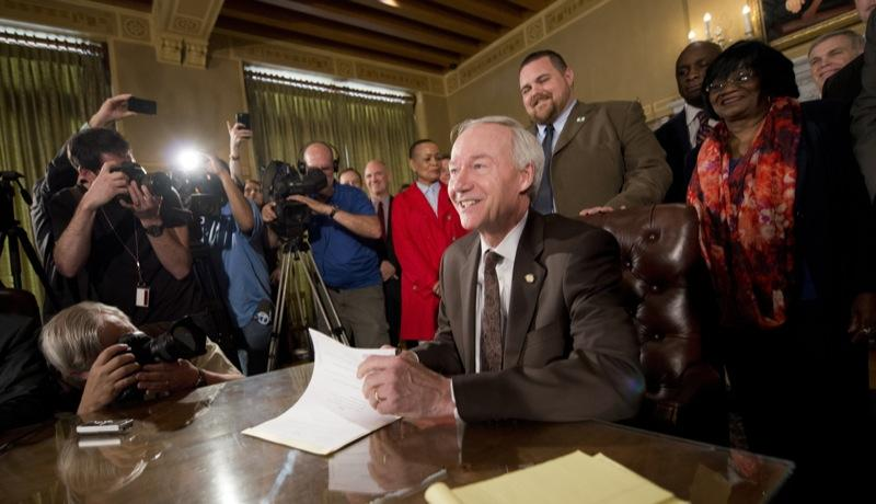 Governor Asa Hutchinson signing the religious objections bill into law Thursday.