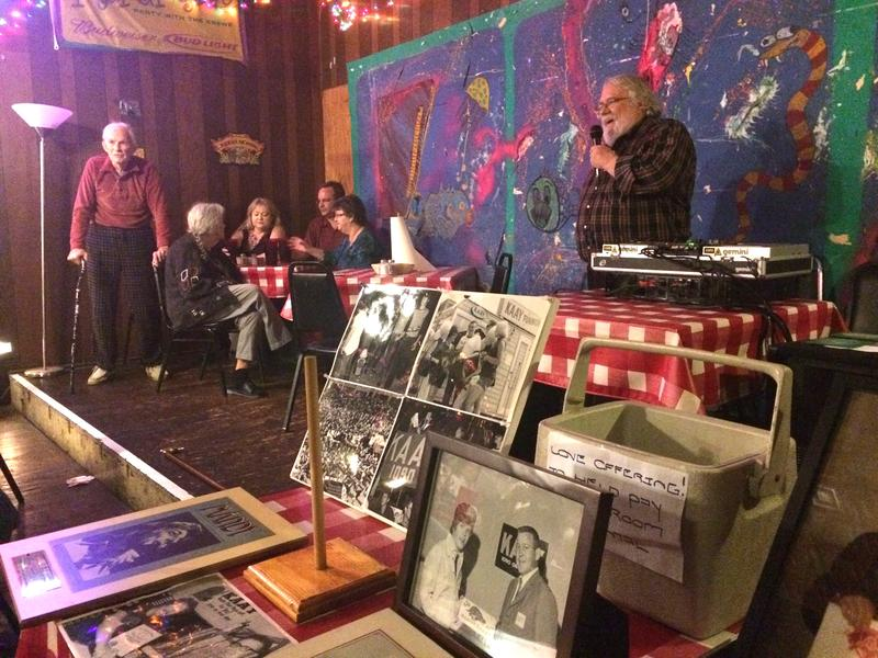 Longtime KAAY chief engineer Felix McDonald (left) listens, while former Beaker Street host Clyde Clifford speaks at Friday night's anniversary event, behind a collection of station photos.