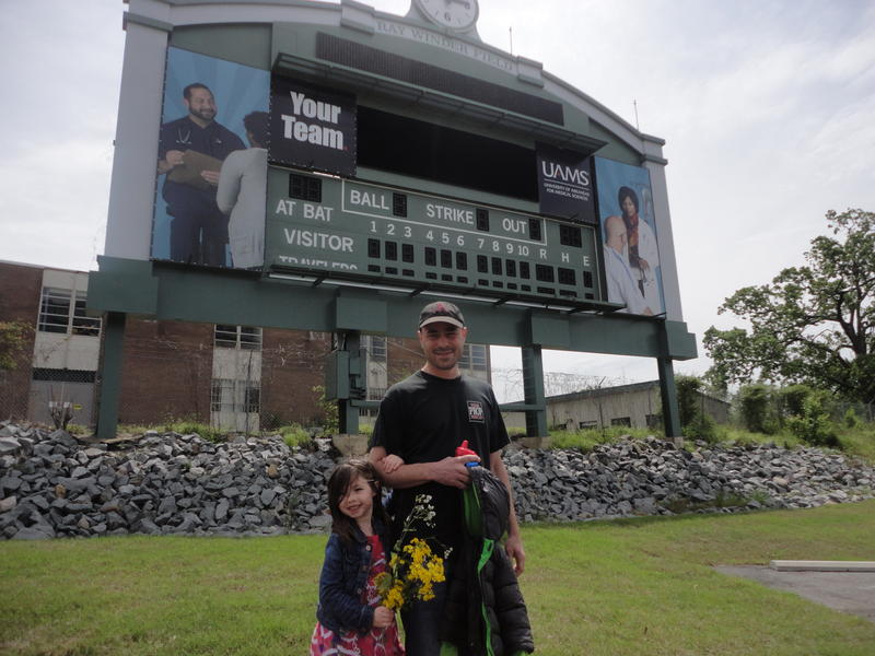Former Arkansas Traveler broadcaster Phil Elson with his daughter under the last piece of Ray Winder Field still standing.