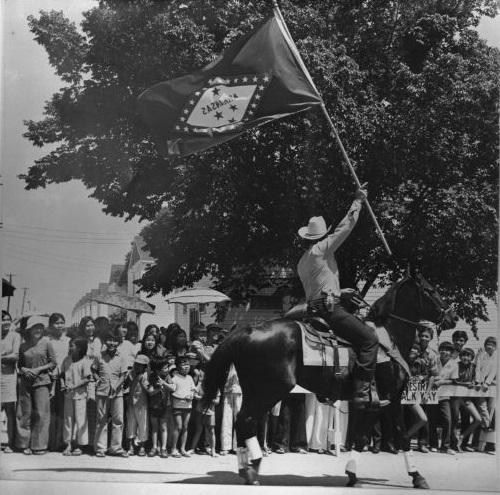 Patrolman parades with Arkansas flag in front of Indochinese refugees at Fort Chaffee