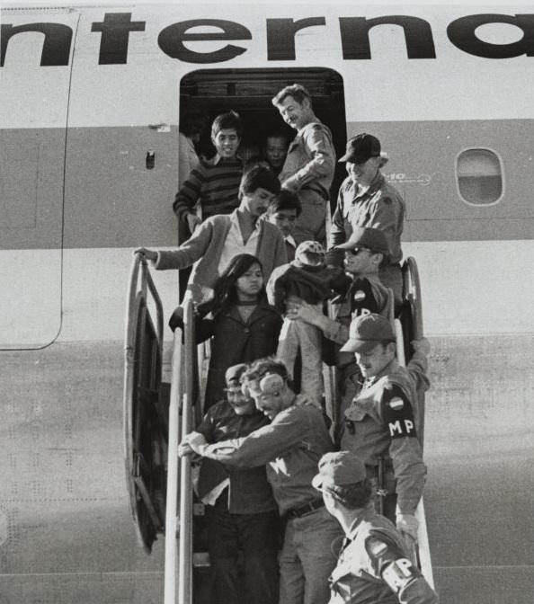 Refugees exit a plane at Fort Chaffee