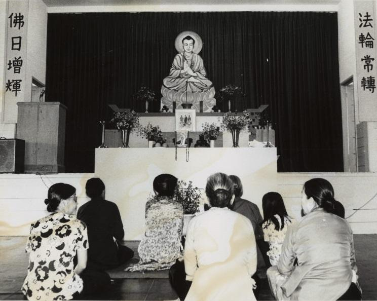 Women kneel in front of Buddha statue at Fort Chaffee